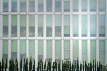 Architectural details of a modern office building with a line of trees