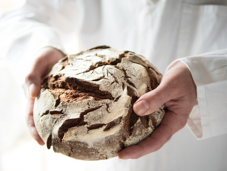 Closeup view of male hands holding a freshly baked round country bread