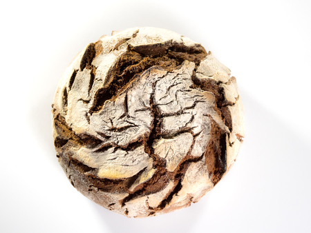 top view of a freshly baked round country bread on white background