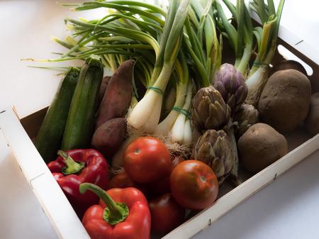 Box of a variety of organic vegetables: potatoes, green onions, tomatoes, red capsicum, sweet potatoes, zucchini and artichokes 版權商用圖片