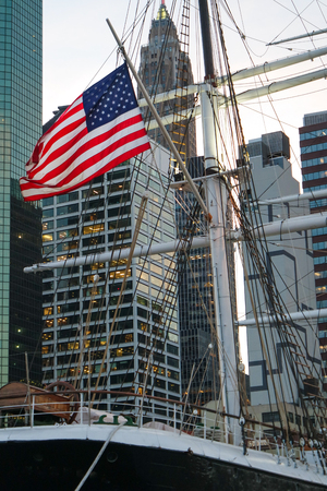 Close up of a US flag on a three masts boat with Manhattan skyscrappers as background 版權商用圖片