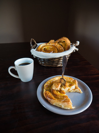 Vertical view of French raisin pastries on a white plate and wicker basket with a cup of coffee on a wooden table 版權商用圖片