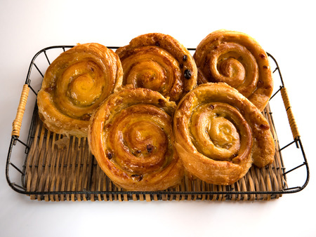 Close up of several French raisin pastries on a wicker trail and white background