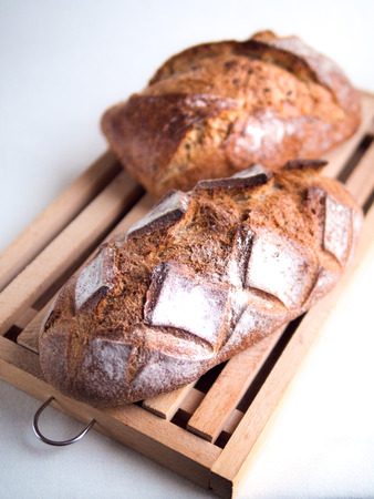 Top view of two whole country breads on a cutting board and white background