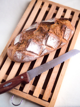 Top view of a whole country loaf on a cutting board with a bread knife