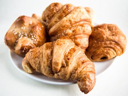 Vue gros plan d & # 39 ; une variété de croissants français et des petits pains sur une plaque blanche et une table Banque d'images - 98300177