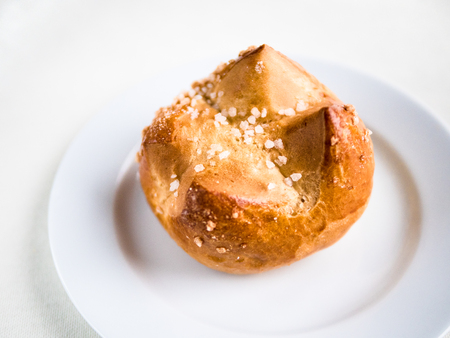 Horizontal view from above of a single  brioche, French  bun, on a white plate and background 版權商用圖片