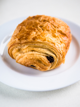 Vertical view of a single French chocolate croissant on a white plate and background