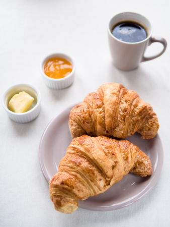 Above view of a Continental breakfast with French croissants, butter, jam and black coffee on white table