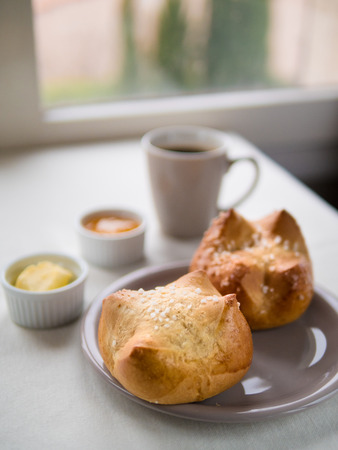 Above view of  of two brioches, French bun with butter, jam and a cup of hot drink in front of a window on a rainy day