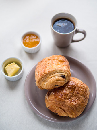 Above view of a Continental breakfast with French chocolate croissants, butter, jam and black coffee on white table Banque d'images - 98281321