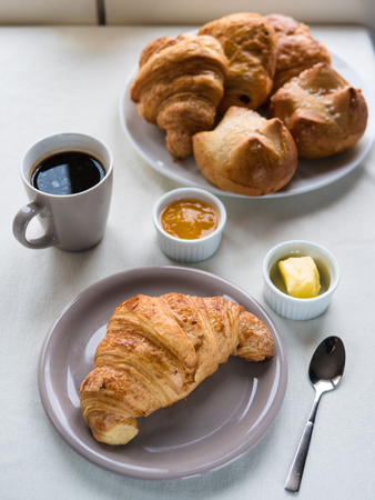 Above view of a Continental breakfast with French croissants, butter, jam, black coffee and a basket of assorted French pastries on white table