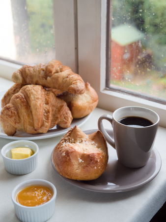 Above view of  a brioche, French bun , croissants, with butter, jam and a cup of coffee in front of a window on a rainy day