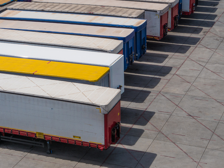 Row of truck containers waiting to be shipped overseas on a parking