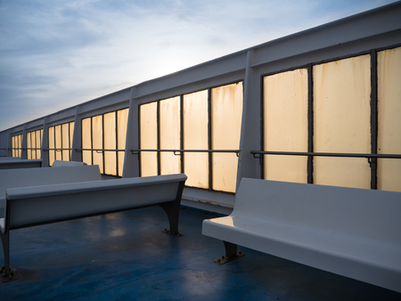 Benches on an empty  ferry deck at sunset