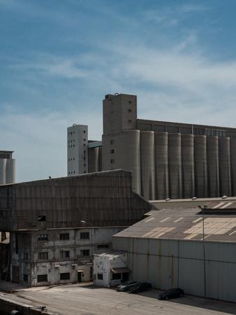 Warehouses, docks, silos in Barcelona cargo port on a sunny day