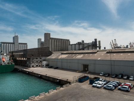 Warehouses, docks, silos and cars in Barcelona cargo port on a sunny day 版權商用圖片