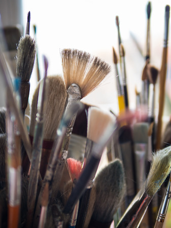 Close up of a variety of used painter brushes