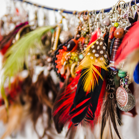 Close up of a variety of woman earrings made of feathers, stones and metal 版權商用圖片