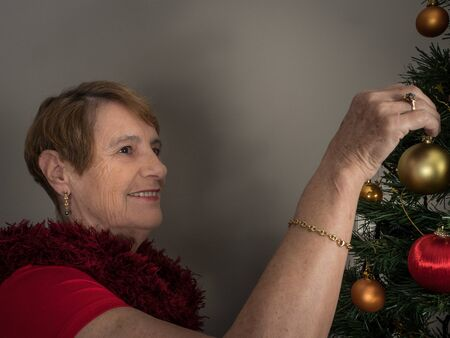 Horizontal portrait of an elderly woman decorating a Christmas tree