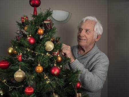 Horizontal portrait of an elderly man decorating a Christmas tree 版權商用圖片