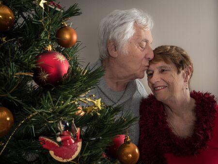 Closeup protrait of an elderly couple kissing by a Christmas tree 版權商用圖片