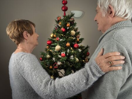 Horizontal portrait of an elderly couple watching a Christmas tree 版權商用圖片