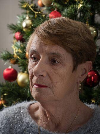 Horizontal portrait of a sad elderly woman by a Christmas tree