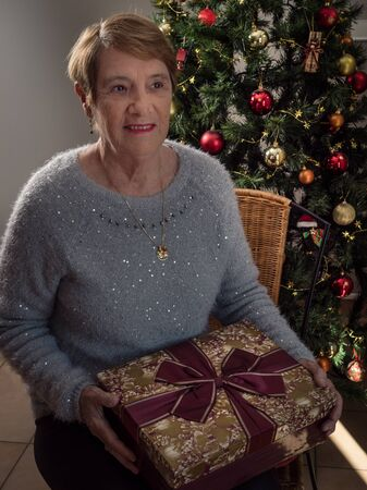 Vertical portrait of an ederly woman with a gift  by Christmas tree