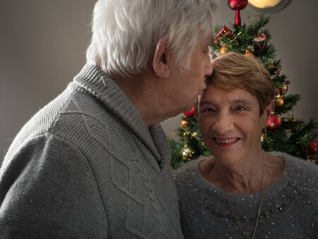 Closeup protrait of an elderly couple kissing in front of a Christmas tree 版權商用圖片