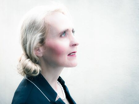 horizontal portrait of a classy mature woman looking into the future with confidence