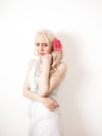 Vertical portrait of a sophisticated blond woman in emotional pain