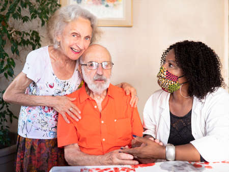 Horizontal portrait of an African American medical assistant helping an ederly couple at home in times of Covid19 pandemic Standard-Bild