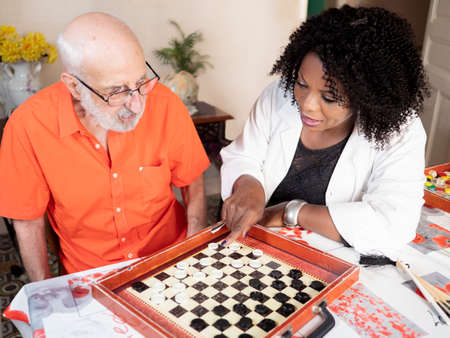 Horizontal portrait of an African American medical assistant playing a board game with an ederly caucasian man