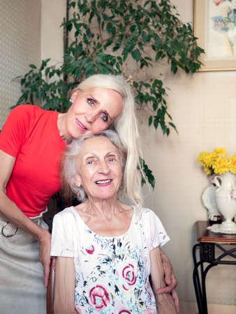 Vertical portrait of a daughter hugging lovingly her elderly mother Stockfoto