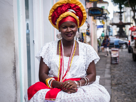 Woman dressed in the traditional clothes of Bahia encourages tourists to enter souvenir shops in Salvador, Brazil