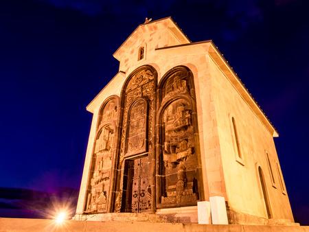 chronicle: Small orthodox church next to the Chronicle of Georgia  Stonehenge  in Tbilisi, Georgia illuminated by night  Stock Photo