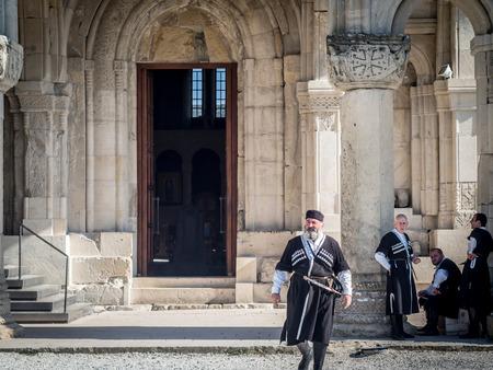 kutaisi: Uomini in abiti tradizionali di fronte alla cattedrale di Bagrati a Kutaisi, Georgia