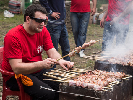 ethnographical: People prepare traditional mtsvadi during Young Wine Festival in Tbilisi, May 2013 Editorial