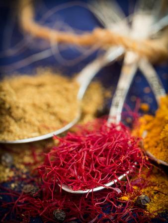 Spices from Zanzibar: turmeric, saffron and cumin on silver spoons. photo