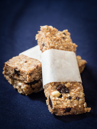 Homemade granola protein bars with peanut butter, honey, nuts, cacao and raisins.