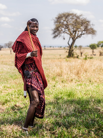 Maasai warrior in Mikumi, Tanzania. The Maasai are a Nilotic ethnic group of semi-nomadic people inhabiting southern Kenya and northern Tanzania.