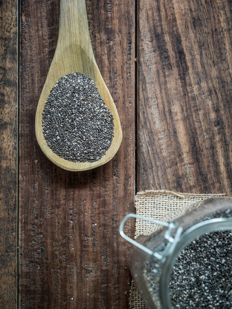 hispanica: Vertical photo of chia (salvia hispanica) seeds on a wooden spoon placed on a rustic wooden background Stock Photo
