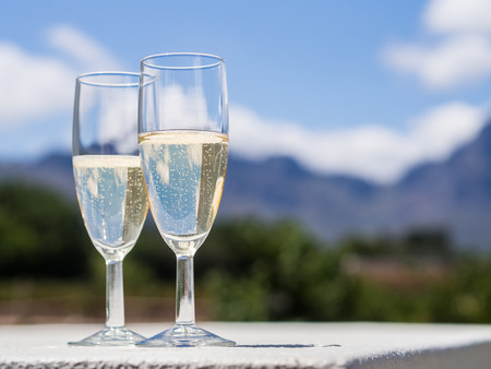 Horizontal photo of two glasses of South African white sparkling wine in a garden of a winery close to Franschhoek in Winelands in Western Cape, South Africa. Vineyard and mountains in the background