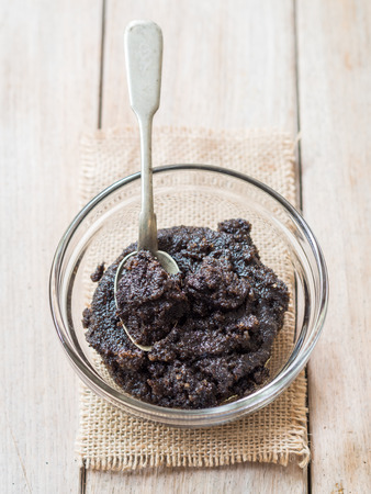 Homemade face and body organic all natural coffee scrub (peeling) with anti cellulite properties in a glass bowl, placed on a wooden table. Silver spoon inside. Vertical orientation. Imagens