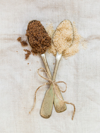 vertical orientation: Muscovado and demerara brown sugars on two silver spoons placed on a rustic linen tablecloth. Vertical orientation. Stock Photo