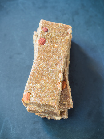 chewy: Homemade organic healthy chewy muesli granola power bars with wholemeal oats, cashew butter, honey and nuts, arranged in a pile. Vertical orientation,overhead view, close up.