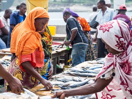 Frauen vor Ort zu kaufen Meeresfrüchten in der Fischmarkt in Dar es Salaam, Tansania in Ostafrika am Sonntag. Querformat.