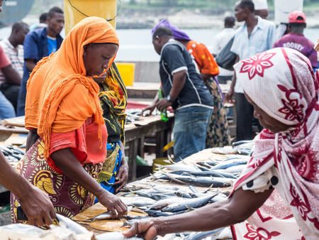 Local women buying seafood in the fish market in Dar es Salaam, Tanzania in East Africa on Sunday. Landscape orientation.