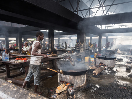 city fish market: Local people frying fish on the fish market in the port in Dar es Salaam, Tanzania, East Africa, on a weekend. Horizontal orientation.